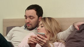 Young couple lying in bed, man using digital tablet, bored woman using smartphone stock footage