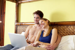 Young couple lying on bed with pc Stock Image