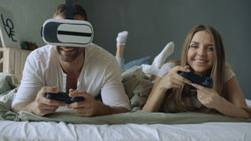 Young couple lying in bed play video games with controller and VR headset stock video footage
