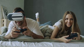 Young couple lying in bed play video games with controller and VR headset stock footage