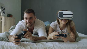Young couple lying in bed play video games with controller and VR headset stock video