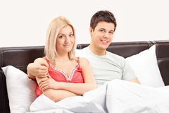 Young couple lying in bed and posing together Stock Images