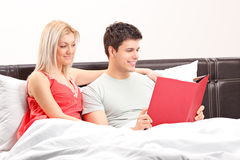 Young couple lying on a bed and reading a book Royalty Free Stock Image