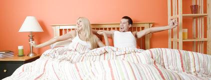 Young Couple Lying in Bed Stretching Royalty Free Stock Images