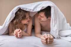 Young couple lying in bed under blanket and looking in their eyes Royalty Free Stock Images