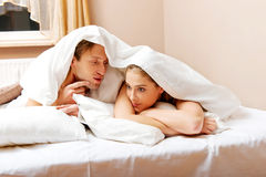 Young couple lying on bed under quilt Stock Photo