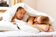 Young couple lying on bed under quilt Royalty Free Stock Photos