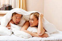 Young couple lying on bed under quilt Stock Photos