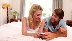Young couple lying on bed using smartphone. At home in the bedroom stock video footage