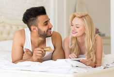 Young Couple Lying In Bed Using Tablet Computer Hold Credit card Online Shopping Payment Stock Photos