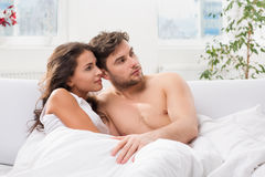 Young couple  lying in bed watching television. Young couple in the morning lying in bed watching television Royalty Free Stock Photo