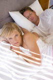 Young couple lying in bed, woman in foreground, portrait Royalty Free Stock Photography