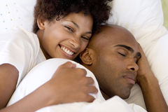 Young couple lying in bed, woman smiling, portrait, elevated view Royalty Free Stock Images