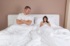 Young couple lying in bed and woman is very small Royalty Free Stock Image