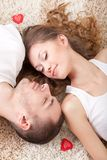 Young couple lying on the carpet Stock Photos