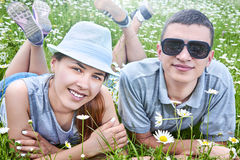 Young couple lying on chamomile meadow Stock Photos