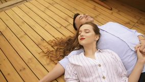 Young couple lying on deck of moving ship on summer day. Girl with long brunette hair in white, traveling on small boat on warm. Sunny day. Beautiful lover stock video