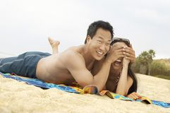 Young couple lying down on beach Stock Photos