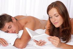 Young couple lying down in bed. Woman reading book Royalty Free Stock Photos