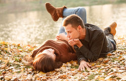Young couple lying down outdoors. Young male and female lying down near lake talking Royalty Free Stock Photo