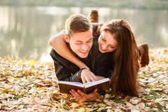 Young couple lying down reading. Young couple lying down near lake reading book smiling Royalty Free Stock Photo