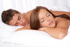 Young couple lying down in white bed Stock Photos