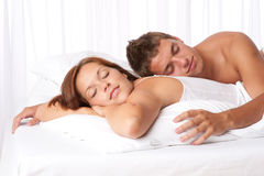 Young couple lying down in white bed Stock Images