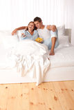 Young couple lying down in white bed Stock Photo