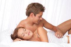 Young couple lying down in white bed Stock Photography