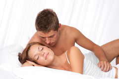 Young couple lying down in white bed Royalty Free Stock Image