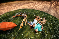 Young couple lying and dreaming on the grass in the park with bi Stock Photography