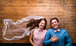 Young couple lying on a floor against wooden background Royalty Free Stock Photography