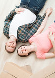 Young couple lying on the floor among boxes Royalty Free Stock Images