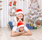 Young couple lying on the floor of decorated christmas room Stock Photos
