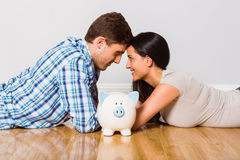 Young couple lying on floor smiling with piggy bank Royalty Free Stock Image