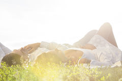 Young couple lying on grass against clear sky Stock Images