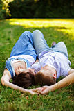 A young couple lying in the grass holding hands Stock Photo