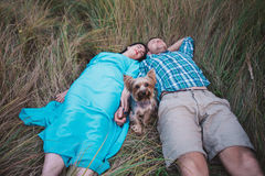 Young couple lying on the grass holding hands and small dog between them Royalty Free Stock Photos