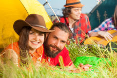 Young couple lying on the grass next to their tent Stock Photography