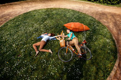 Young couple lying on the grass and riding the bicycle with red Royalty Free Stock Photo