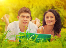 Young couple lying on grass smiling and looking at camera Royalty Free Stock Photography
