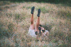 Young couple lying in grass stretching their legs up. Young couple fools around in the meadow Royalty Free Stock Photo