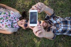 Young couple lying on grass taking selfie Stock Photo