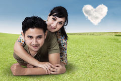Young Couple Lying On Green Grass Stock Image