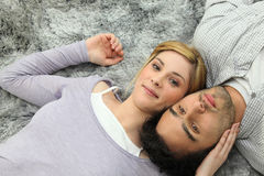 Young couple lying on grey carpet Stock Photos