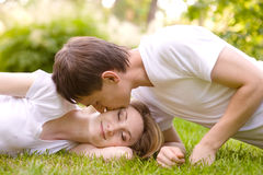 Young couple lying head to head on the grass Royalty Free Stock Images