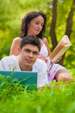 Young couple lying with laptop and book at park Stock Photography