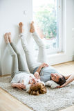 Young couple lying in living room on carpet Stock Image