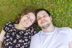 Young couple is lying and relaxing in grass Royalty Free Stock Photo