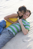 Young couple lying in sand at beach royalty free stock photography